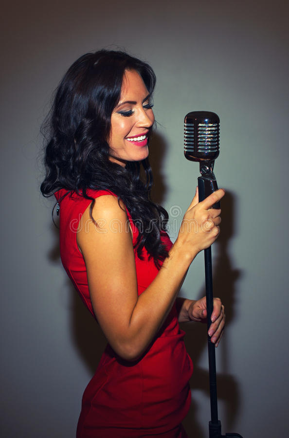 Attractive brunette woman singing. Attractive brunette woman singing into vintage microphone royalty free stock photo