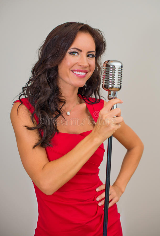 Attractive brunette woman singing. Attractive brunette woman singing into vintage microphone royalty free stock photos