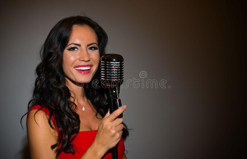 Attractive brunette woman singing. Attractive brunette woman singing into vintage microphone royalty free stock images