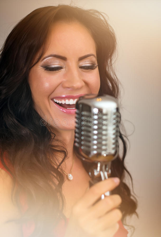 Attractive brunette woman singing. Attractive brunette woman singing into vintage microphone royalty free stock image