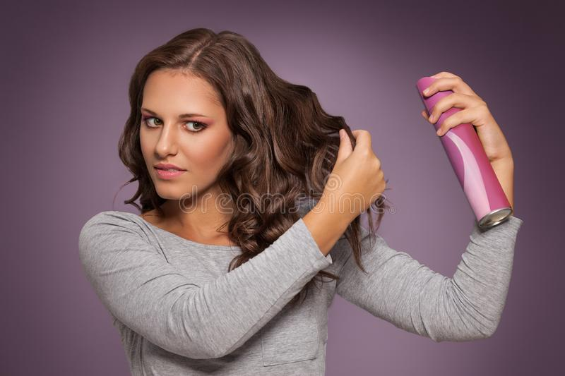 Attractive brunette woman styling her shiny hair stock photo