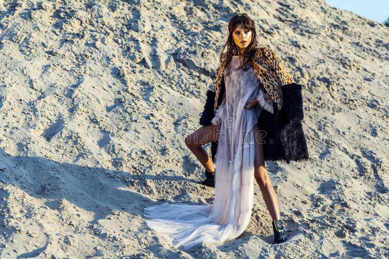 Attractive brunette woman in translucent beach long cover up with leopard fur coat posing on sandy beach at sunset. standing and royalty free stock image