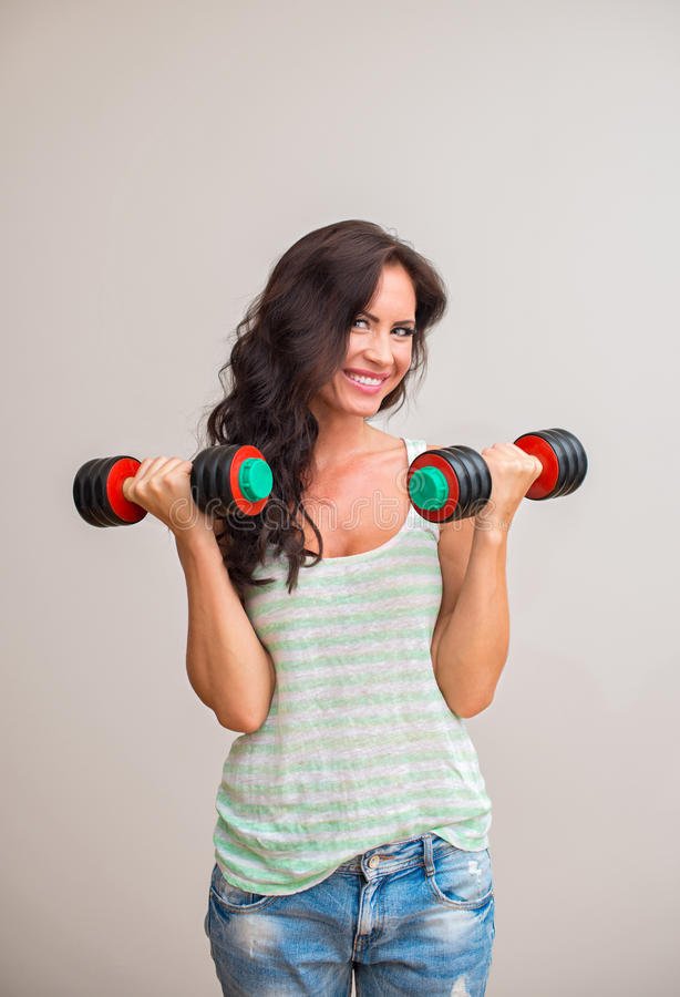 Attractive brunette woman working out. Attractive brunette woman working out with dumbbells royalty free stock image
