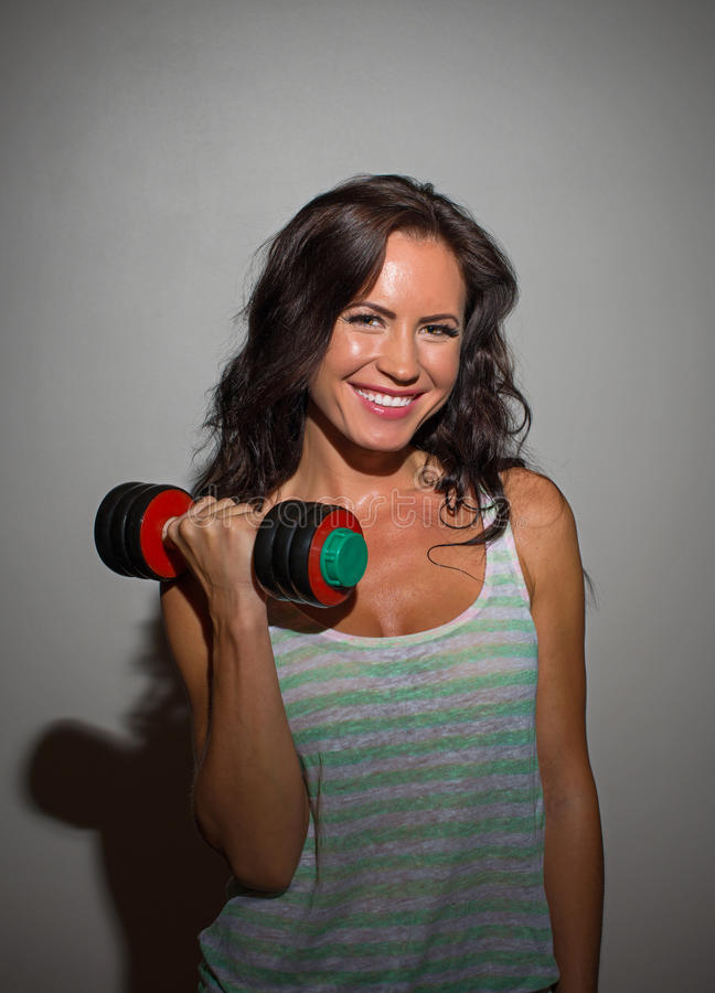 Attractive brunette woman working out. Attractive brunette woman working out with dumbbells stock photos