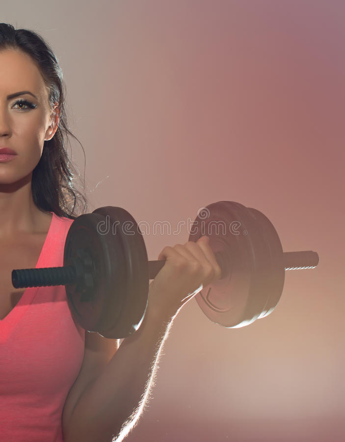 Attractive brunette woman working out. Attractive brunette woman working out with dumbbells stock image