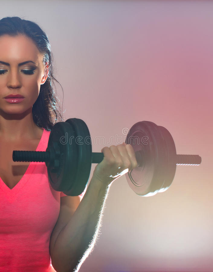 Attractive brunette woman working out. Attractive brunette woman working out with dumbbells royalty free stock photo