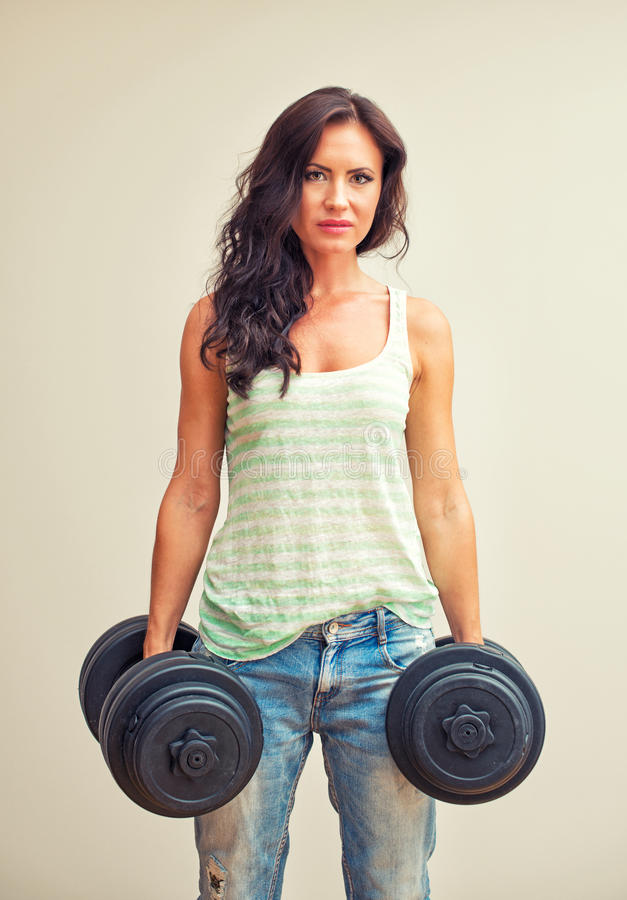 Attractive brunette woman working out. Attractive brunette woman working out with dumbbells royalty free stock photography