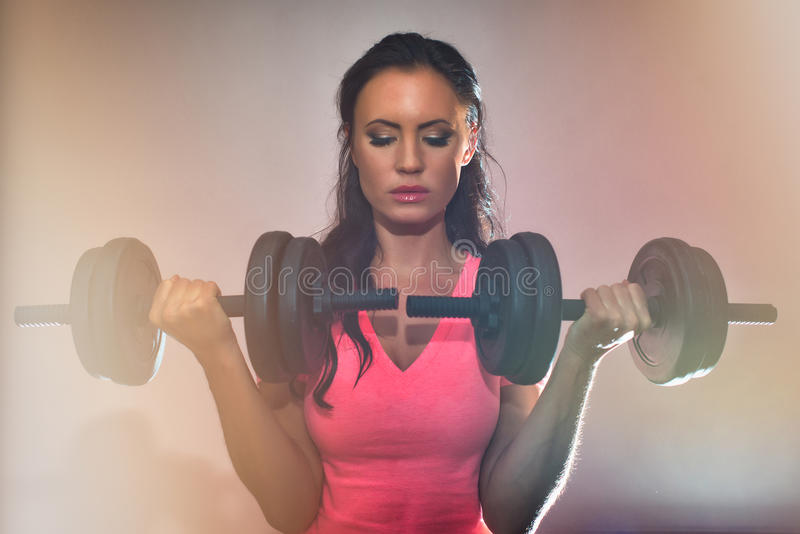 Attractive brunette woman working out. Attractive brunette woman working out with dumbbells stock photography
