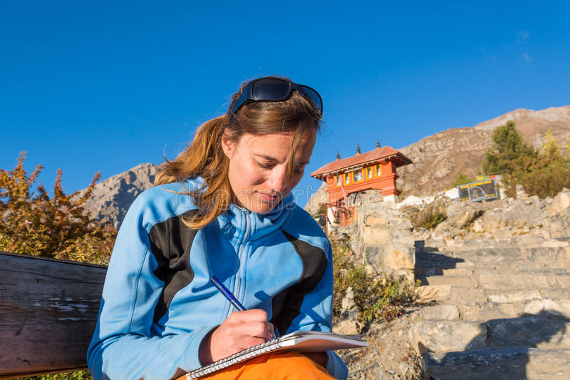 Attractive brunette writting a travel diary. royalty free stock image