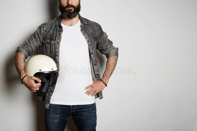 Attractive Brutal bearded male model poses in black jeans shirt and blank white t-shirt premium summer cotton with moto. Helmet in hands, on white background stock photography