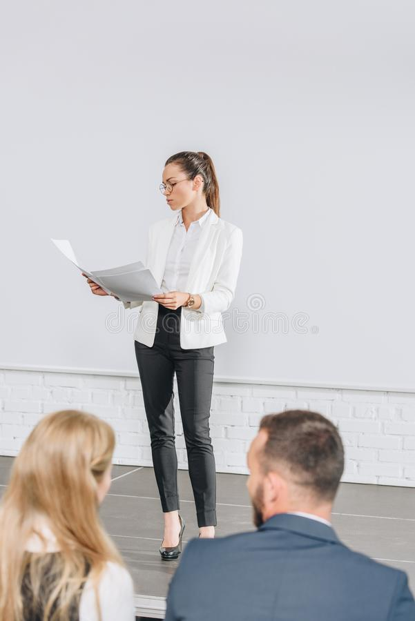 attractive business coach standing on stage and looking at documents during training royalty free stock photos