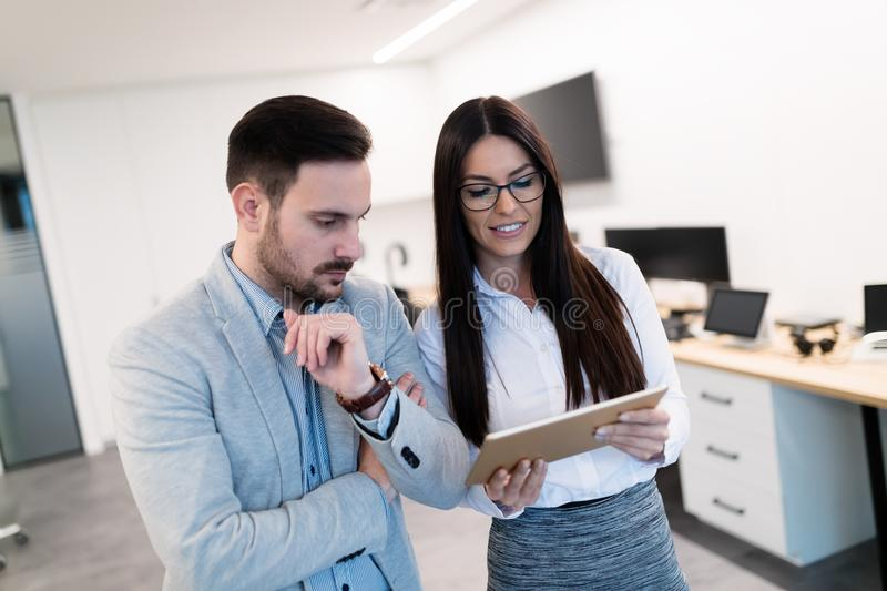 Attractive business couple using tablet in modern office stock photography