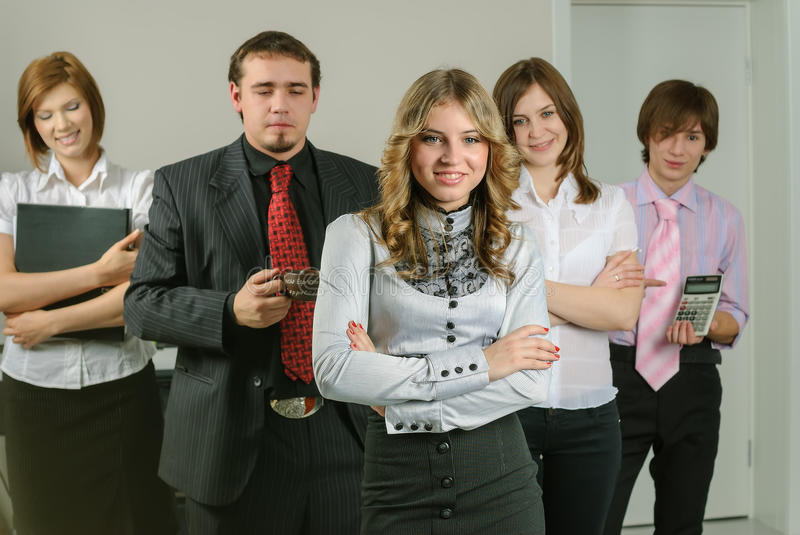 Attractive business lady and her team. Young business team with beautiful chief in office royalty free stock photography