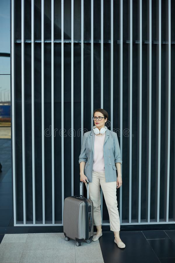 Attractive business lady with wheeled suitcase. Serious attractive business lady with white wired headphones standing in modern airport and holding handle of royalty free stock image