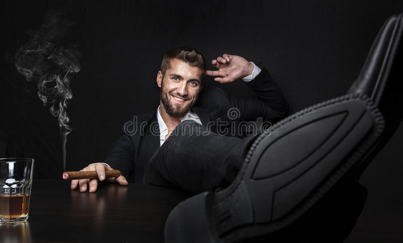Attractive business man with cigar and a drink royalty free stock photos