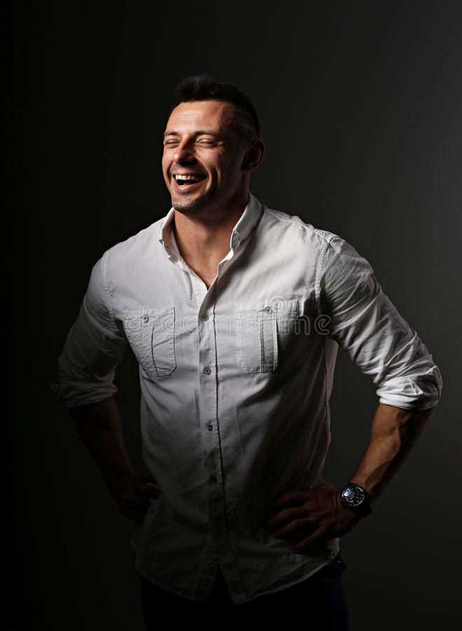 Free Attractive Business Man Laughing With Wide Opened Mouth And Sporty Biceps Arms In White Style Shirt On Dark Shadow Background. Cl Stock Images - 128977524