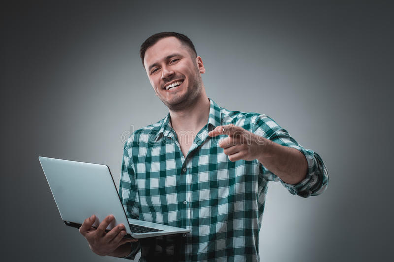 Attractive business man model in green shirt on gray working with laptop, showing something by left hand. Caucasian guy royalty free stock image
