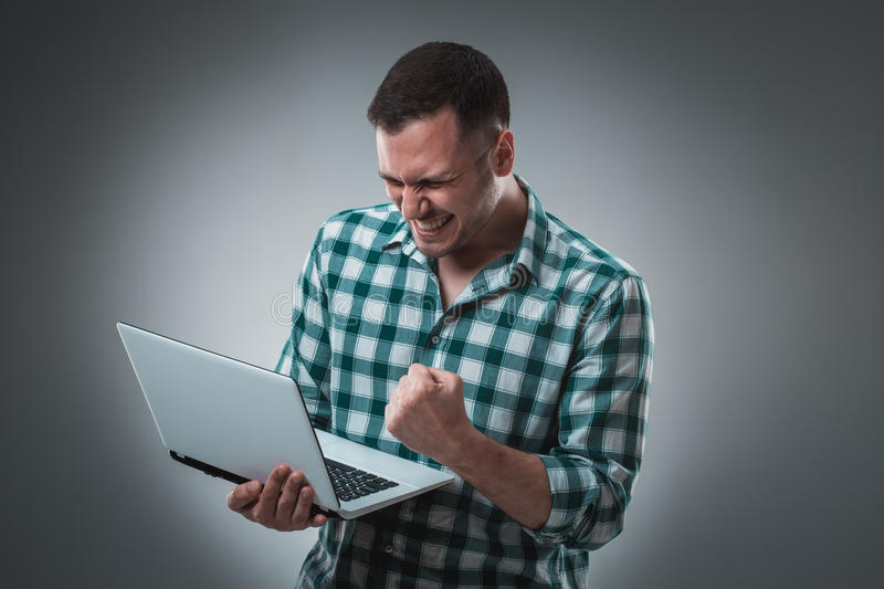 Attractive business man model in green shirt on gray working with laptop, showing something by left hand. Caucasian guy stock image