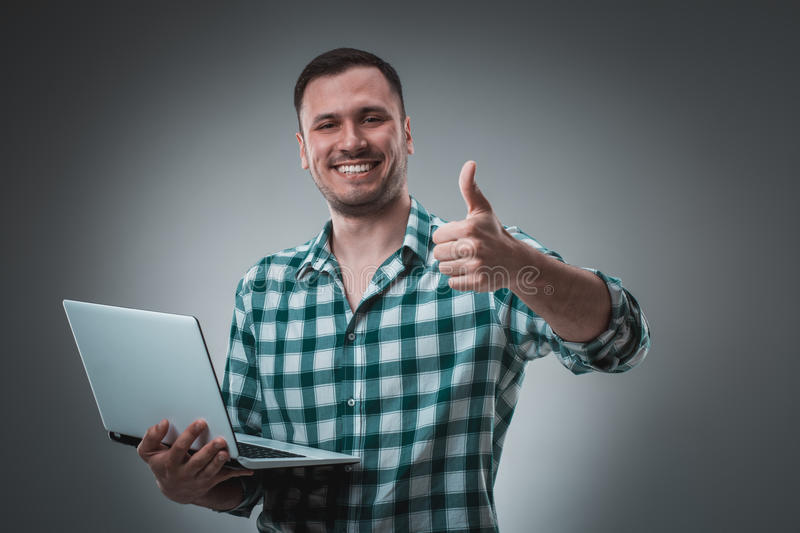Attractive business man model in green shirt on gray working with laptop, showing something by left hand. Caucasian guy stock photography