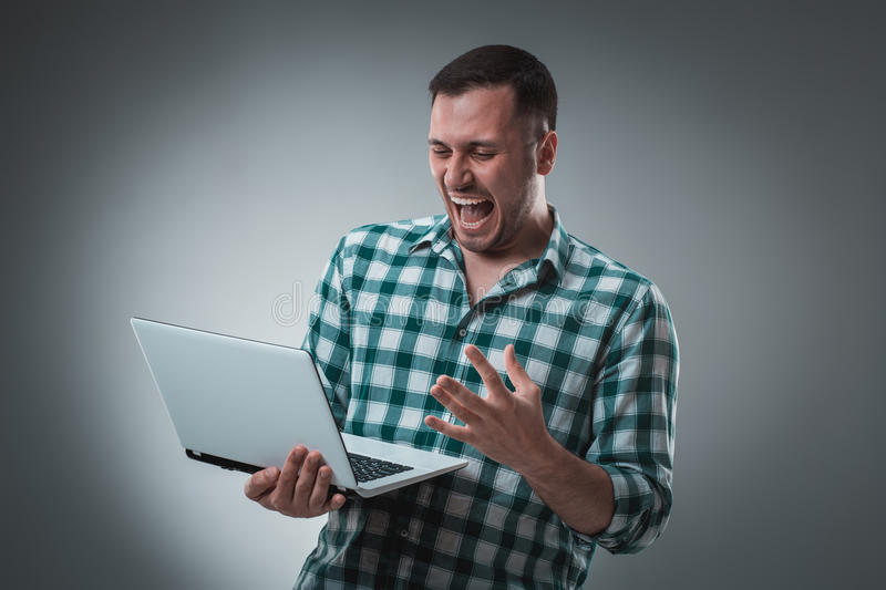 Attractive business man model in green shirt on gray working with laptop, showing something by left hand. Caucasian guy royalty free stock photography