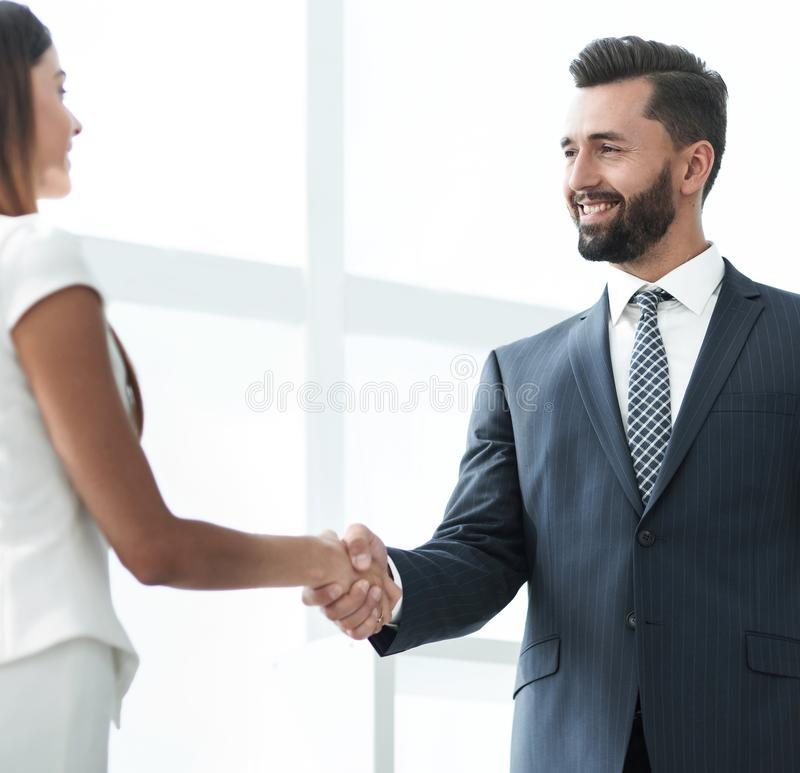 An attractive business man and woman team shaking hands. Friendly senior businessman handshaking with young businesswoman in office royalty free stock photo