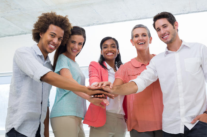 Attractive business people uniting at work. Attractive business people joining hands in the workplace to unite as one while smiling at the camera royalty free stock images