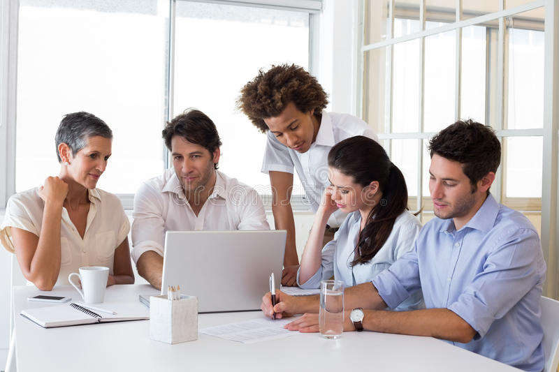 Attractive business people working plans. Attractive business people working hard and discussing at a business meeting stock photo