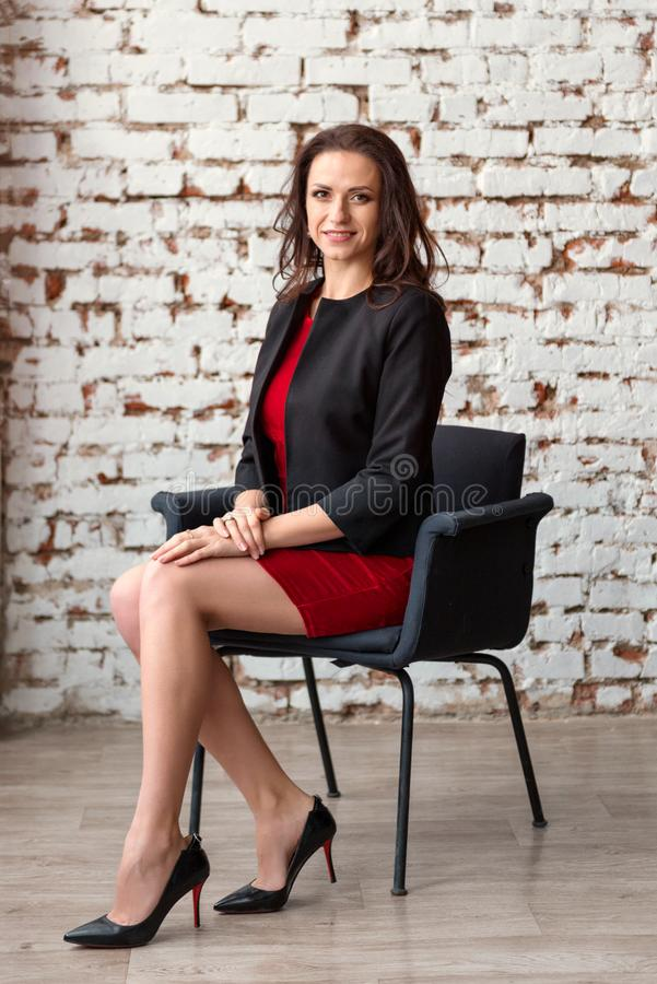 A young attractive business woman brunette in a short red dress and black jacket sitting on a chair with a white wall on the royalty free stock image