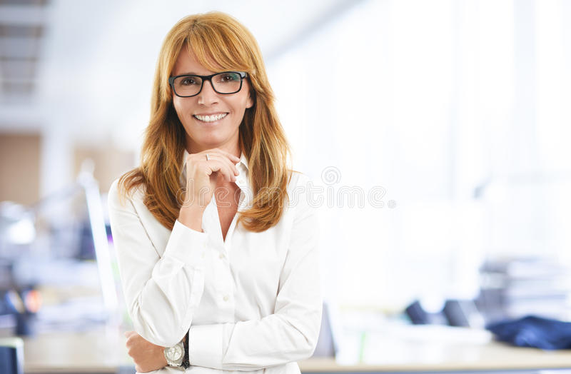 Attractive business woman. Close-up portrait of confident business woman standing at office. Business people stock images