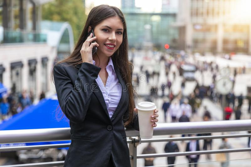 Attractive business woman in the financial district Canary Wharf of London, United Kingdom. Attractive business woman talking to mobile phone and holding a royalty free stock photography
