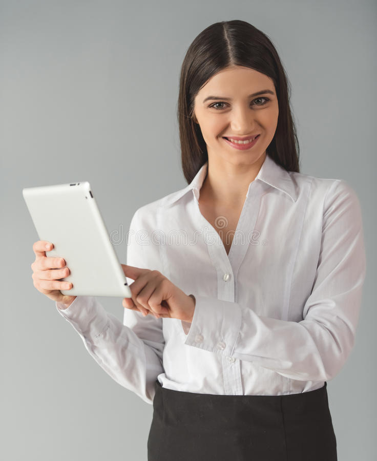 Attractive business woman. In formal clothes is using a digital tablet, looking at camera and smiling, on gray background royalty free stock image