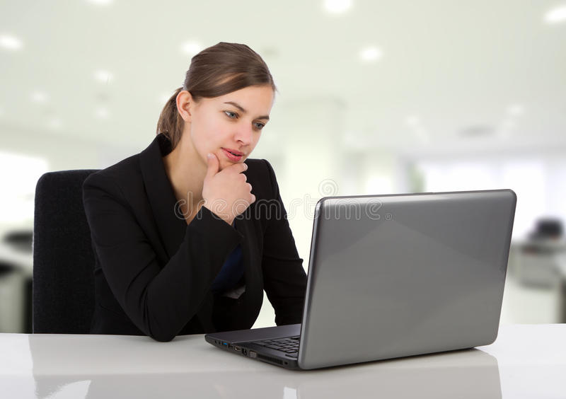 Attractive business woman looking at her laptop screen. In an office environment stock photography