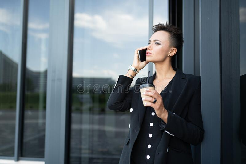 Attractive business woman talking on the phone against the background of the entrance at the office building royalty free stock photo