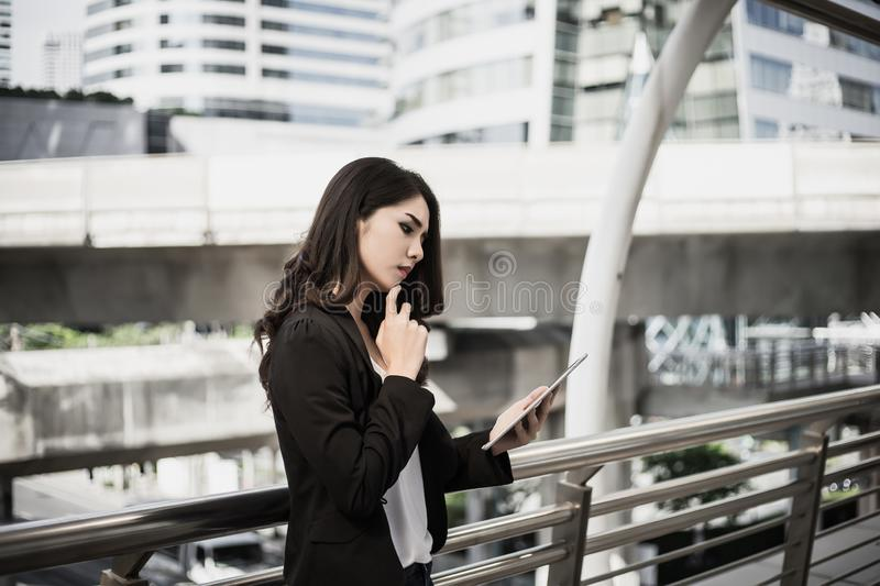 Attractive business woman using a digital tablet while standing in front of office stock photos