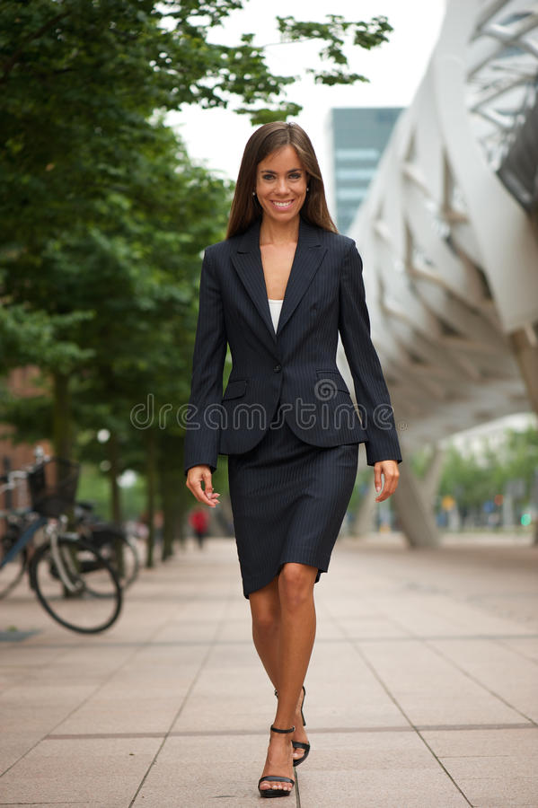 Attractive business woman walking in the city stock images