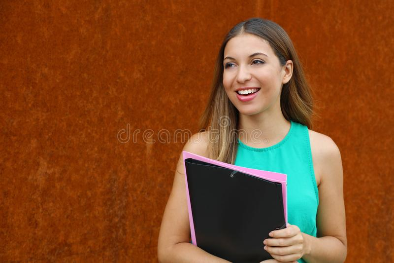 Attractive business woman walking in the street holds folders and  looking to the side the copy space stock image