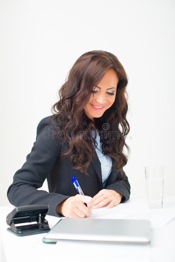 Attractive business woman working. Attractive business woman working with documents in office royalty free stock photography
