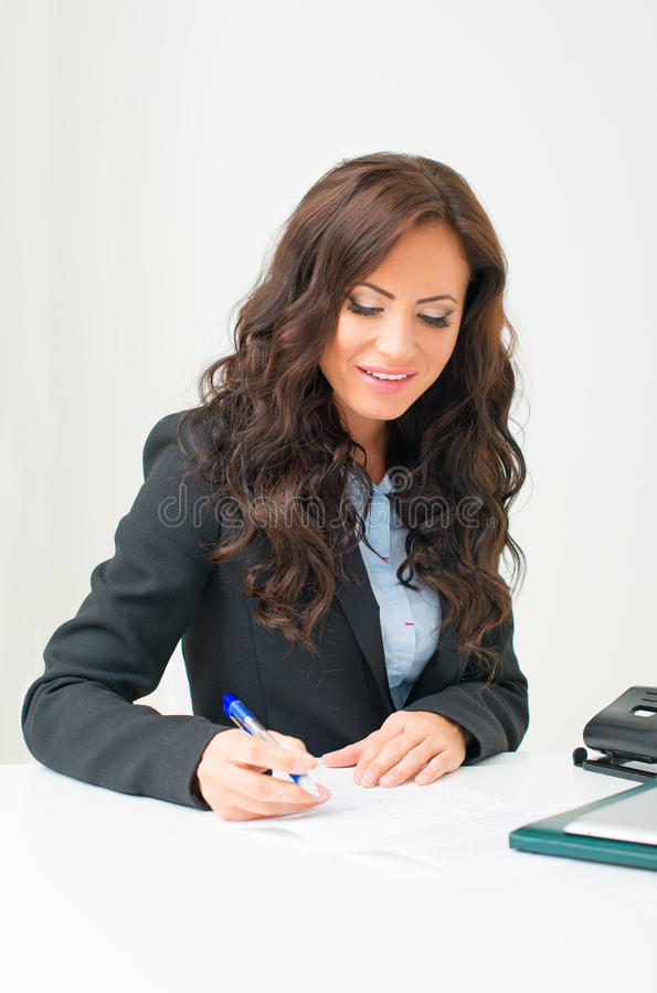 Attractive business woman working. Attractive business woman working with documents in office royalty free stock photos