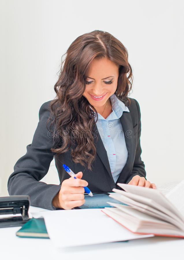 Attractive business woman working. Attractive business woman working with documents in office royalty free stock photo