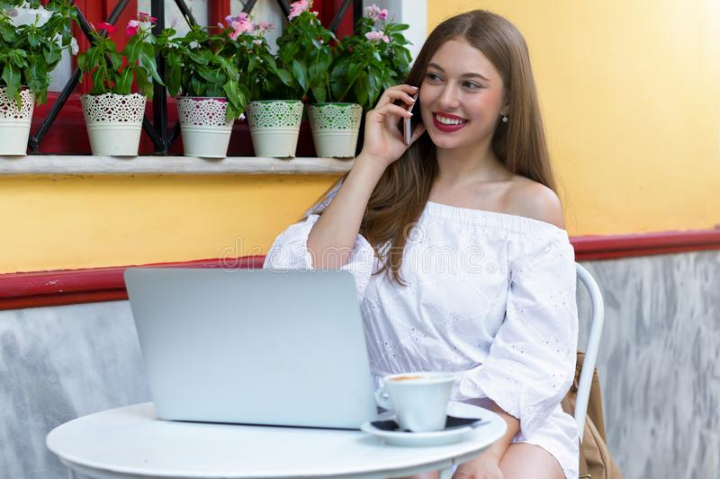 Attractive business woman works outside in a coffee shop royalty free stock images