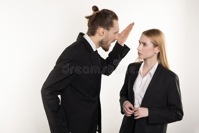 Attractive businessman with beard and trendy hairstyle in black suit screaming at his subordinate who can`t cope the royalty free stock images