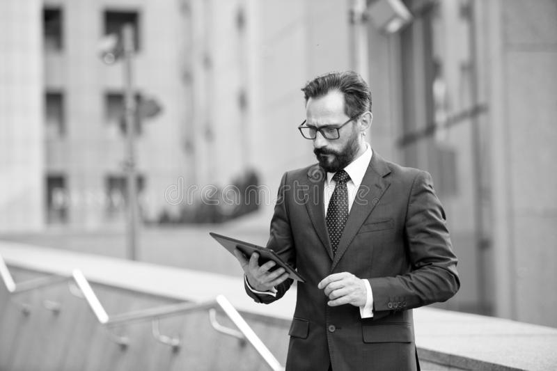Attractive businessman check or read digital tablet outside office building. Social communicate technology in business concept, Li. Festyle of modern business stock photography