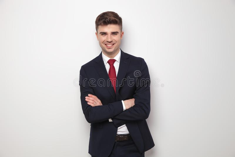 Attractive businessman in navy suit standing with arms crossed royalty free stock photography