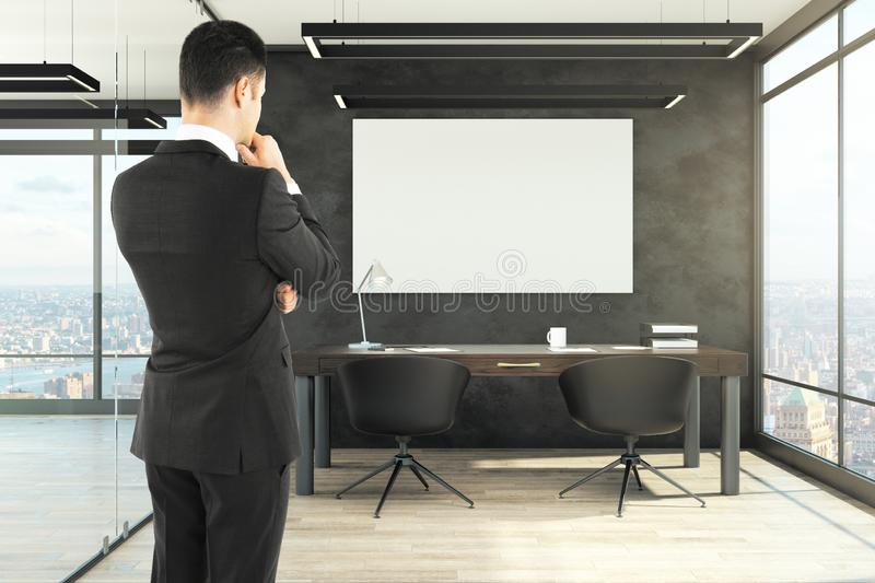 Attractive businessman in office. Attractive businessman standing in modern office interior with empty poster. Mock up royalty free stock photos