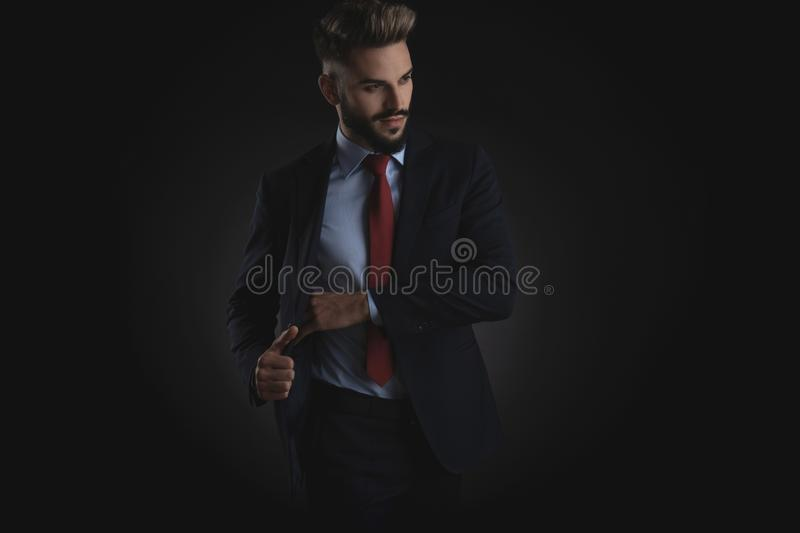 Attractive businessman picks something from inner pocket royalty free stock photo