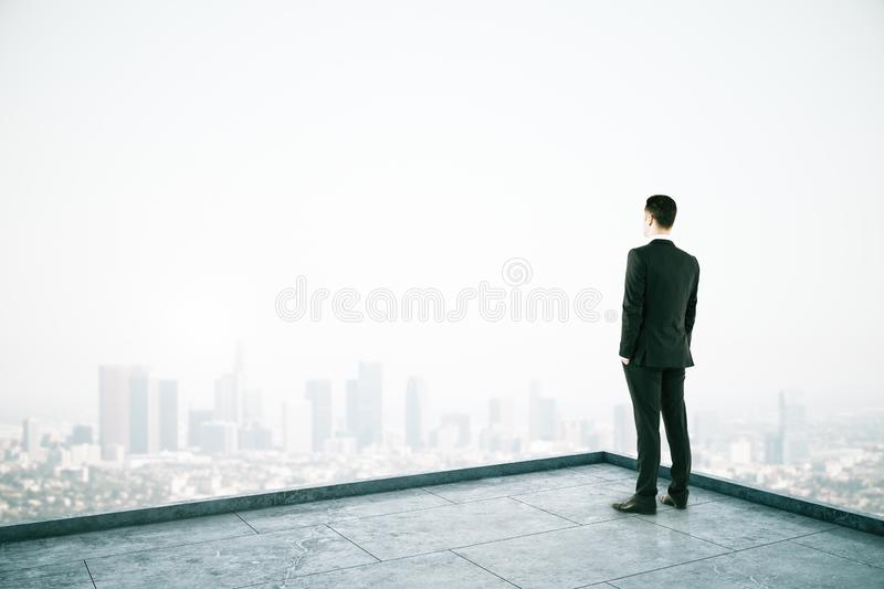 Attractive businessman on rooftop. Attractive businessman looking into the distance on rooftop with daylight city view. Copy space. Success, vision and future royalty free stock photography