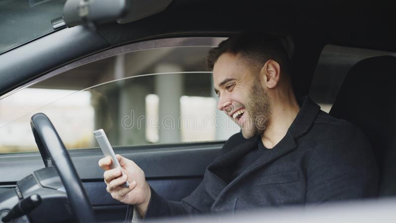 Attractive businessman sitting inside car laughing while using smartphone after trip stock photo