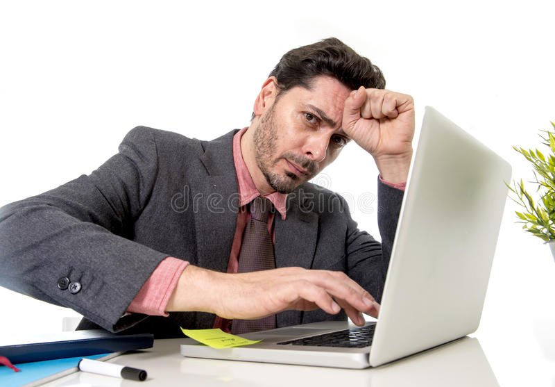 attractive businessman in suit and tie working in stress at office computer laptop looking desperate and frustrated in work and b royalty free stock images