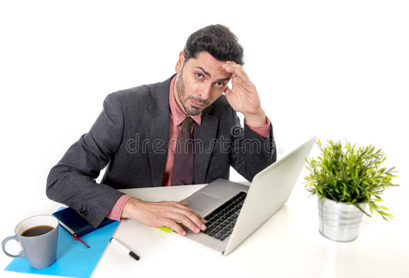 Attractive businessman in suit and tie working in stress at office computer laptop looking desperate and frustrated in work and bu royalty free stock photography