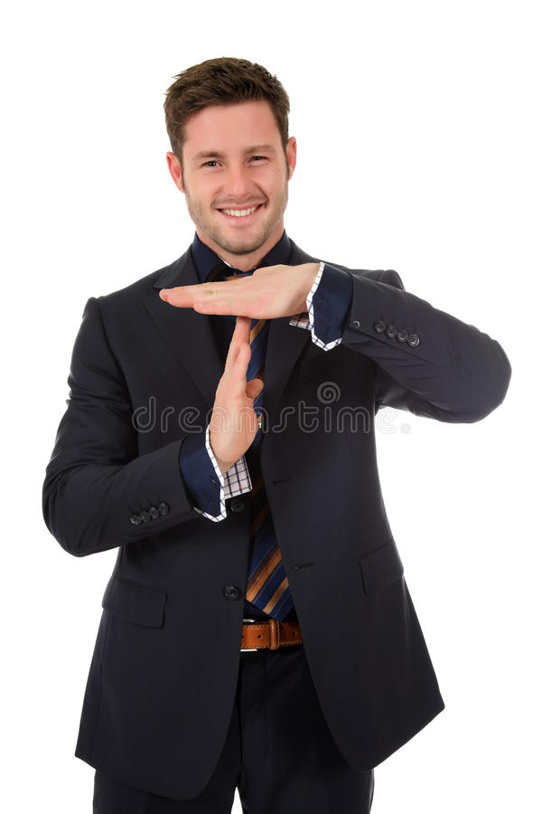 Attractive businessman time out symbol. Attractive young caucasian businessman showing time out symbol. Studio shot. White background stock images